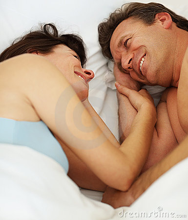 Happy couple lying besides each other on bed