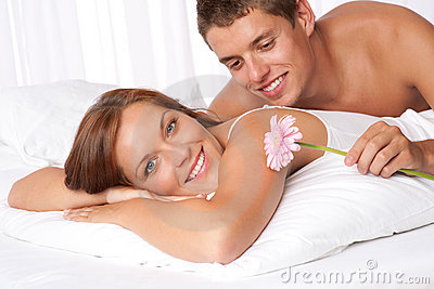 Happy couple lying down in bed together