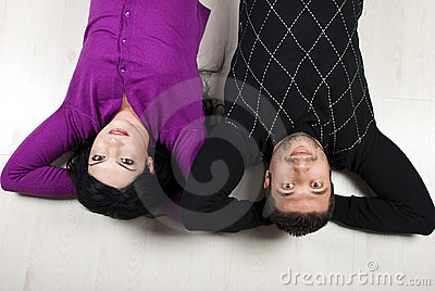 Happy couple lying down on floor