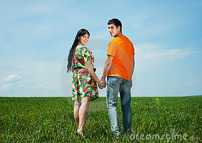 Happy couple in meadow over blue sky