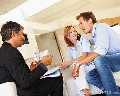 Happy couple in meeting with a estate agent