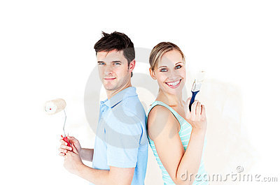 Happy couple with paintbrush standing back to back