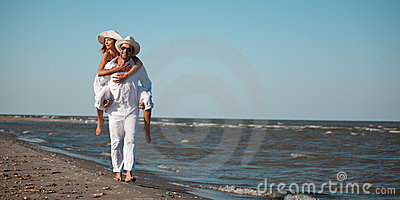 Happy couple piggyback ride on sea shore