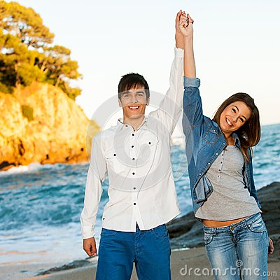 Happy couple raising arms at seaside.