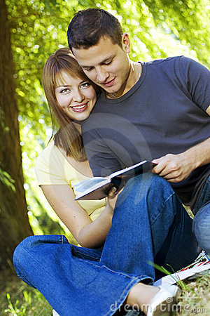 Happy couple reading a book outdoors