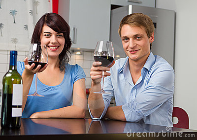 Happy couple with red wine at home