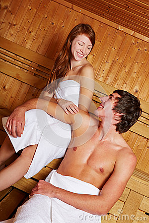 Happy couple relaxing in sauna