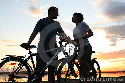 Happy couple riding bicycles outside, healthy life