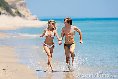 Happy couple running on beach