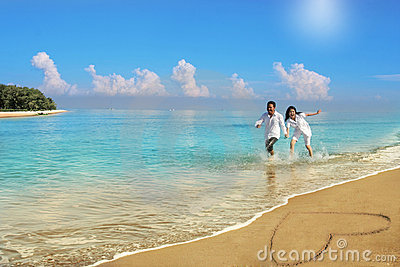 Happy couple running at beach