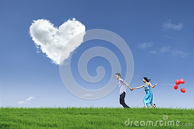 Happy couple running in field with balloons