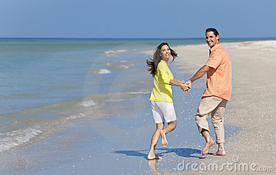 Happy Couple Running Holding Hands on A Beach