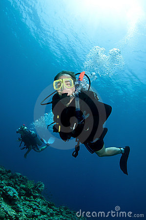 Happy couple scuba dive together