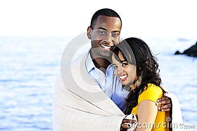 Happy couple sharing blanket