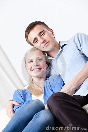 Happy couple sits on the white leather sofa