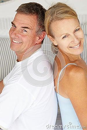 Happy couple sitting back to back
