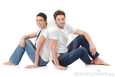 Happy couple sitting with back to each other Stock Photo