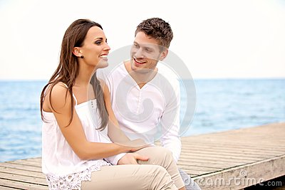 Happy Couple Sitting on a Pier