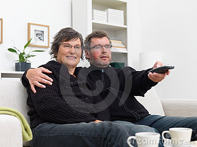 Happy couple sitting on sofa and watching TV