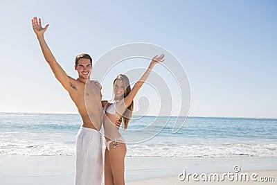 Happy couple smiling at camera and waving