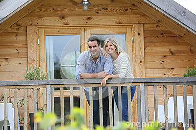 Happy couple standing on terrace of log cabin Stock Photo