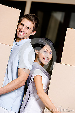Happy couple stands back to back with packages