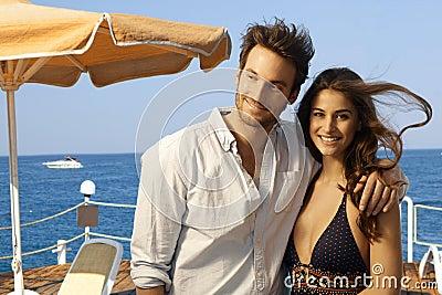 Happy couple at at summer holiday beach pier