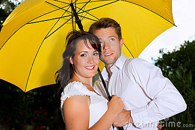 Happy couple in the summer rain with umbrella