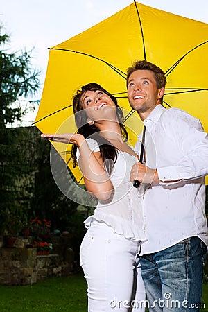 Happy couple in the summer rain with umbrella