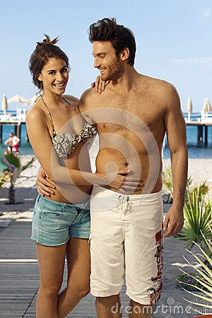 Happy couple in swimsuit at holiday beach resort