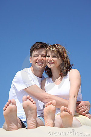 Happy couple with toes up sitting on sand