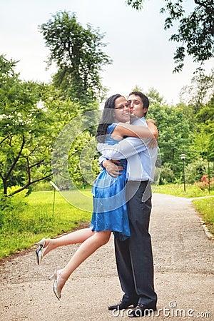 Happy couple - two joyful lovers embracing outdoor