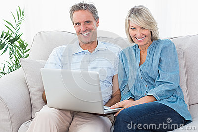 Happy couple using laptop together on the couch looking at camer
