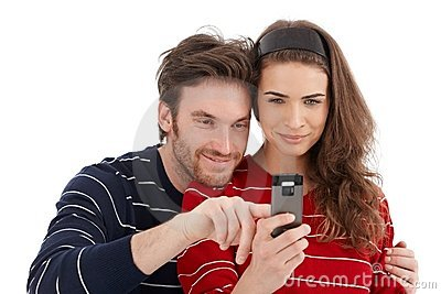 Happy couple using mobile phone smiling