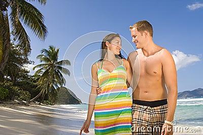 Happy couple walking along a tropical beach