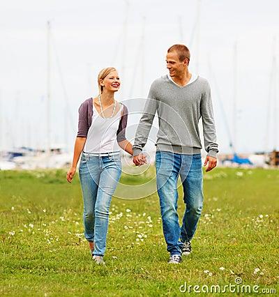 Happy couple walking on a grass field