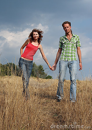 Free Happy Couple Walking On A Field Stock Image - 12400511