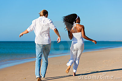 Happy couple walking and running on beach