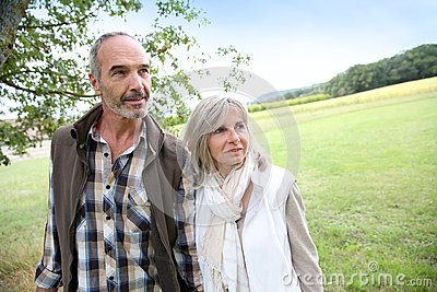 Happy couple walking together in fields