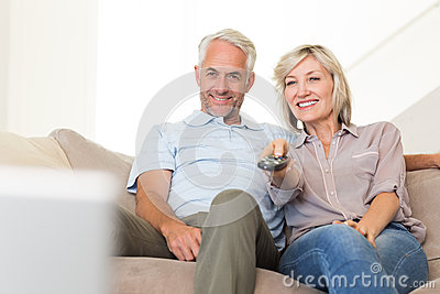Happy couple watching tv on sofa