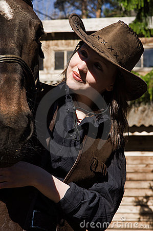 Happy cowgirl with brown horse