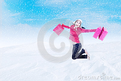 Happy customer jumping with bags in winter snow