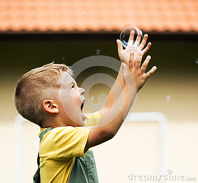 Happy cute kid with soap bubble