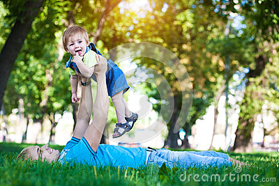 Happy daddy with  baby in a greenl summer park