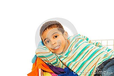 Happy dark skinned boy in clothes basket