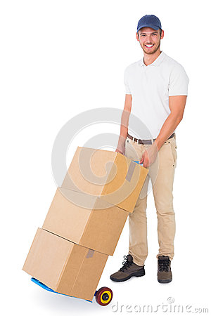 Happy delivery man pushing trolley of boxes