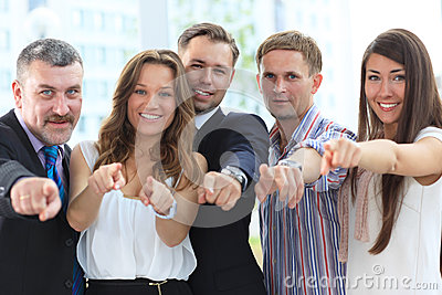 Happy diverse group pointing at you