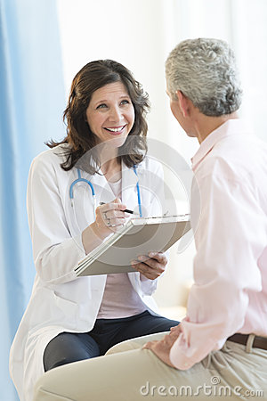 Happy Doctor With Clipboard Looking At Patient