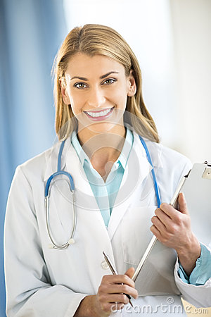 Happy Doctor Holding Clipboard In Clinic