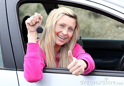 Happy driver showing a key after buying a new car